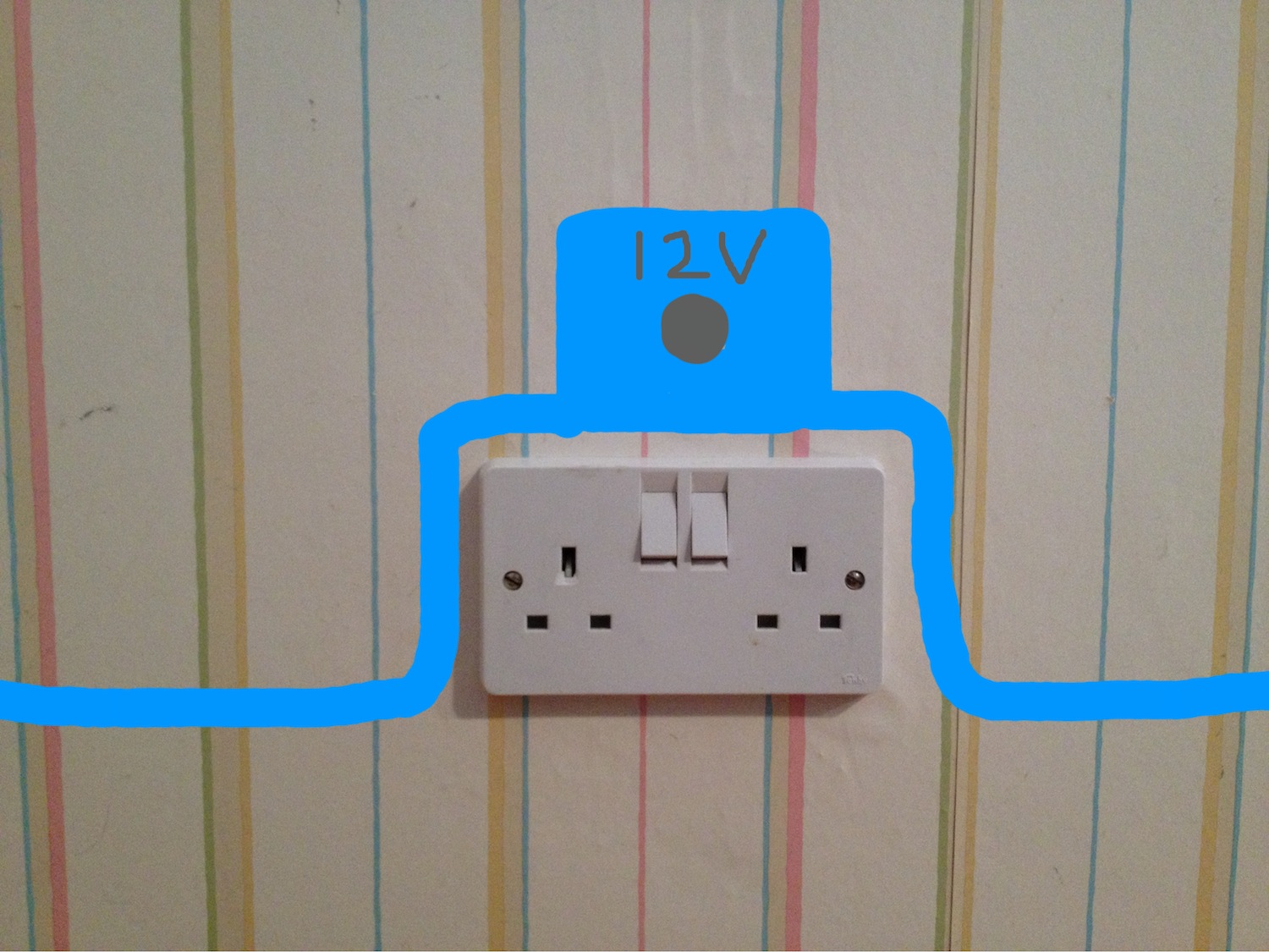 An electricity socket, shown just above two standard UK plug sockets, labelled '12V'