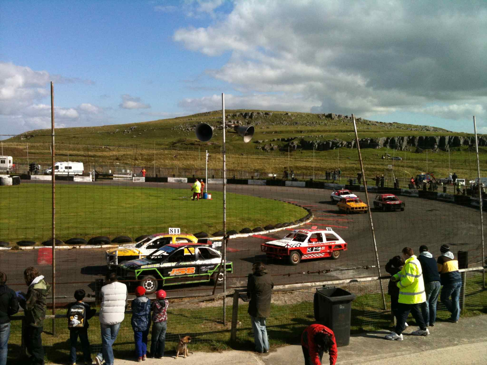 Stockcars racing around the corner of a track, with a rocky hill as the backdrop