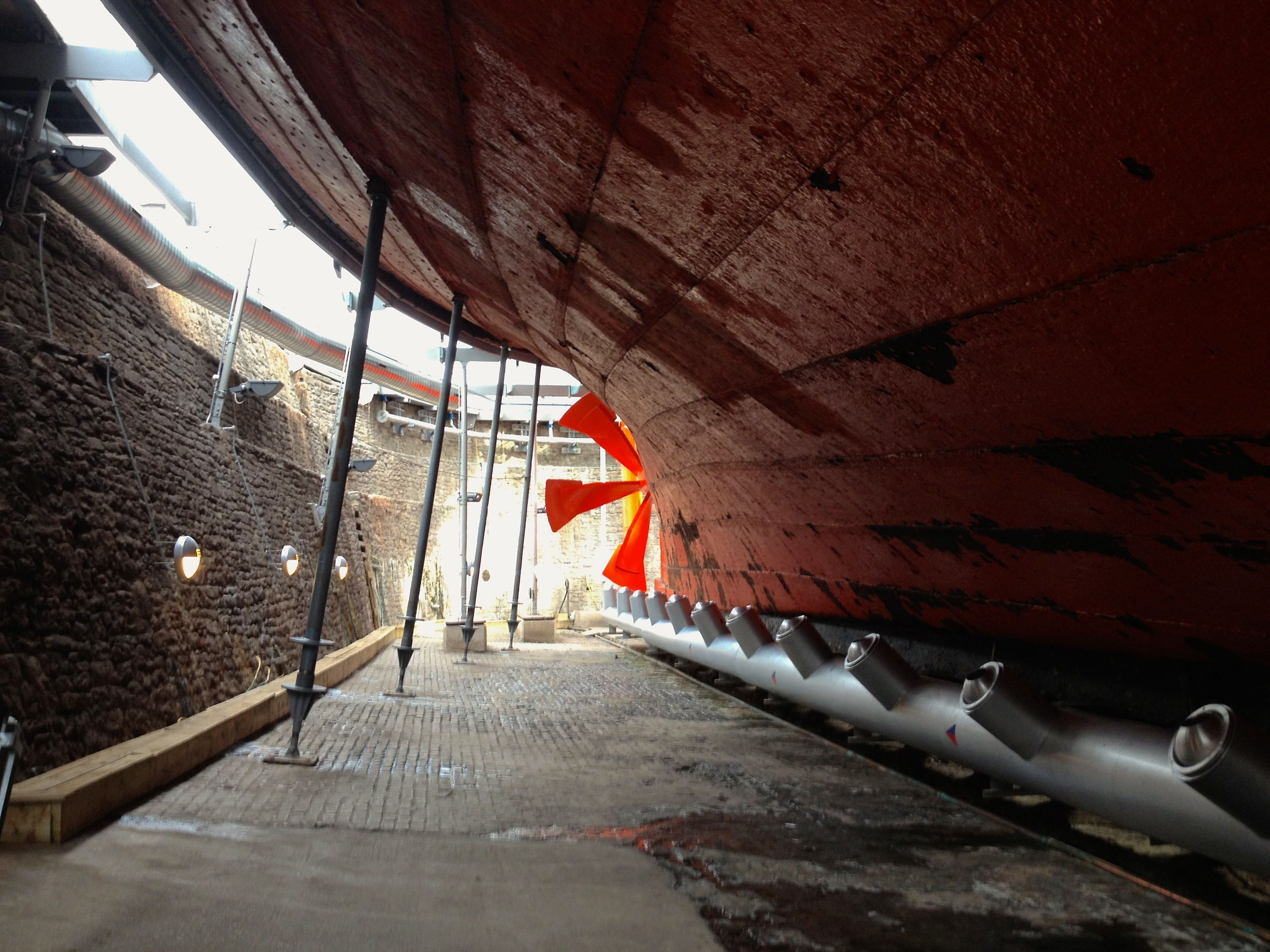 The rusting hull and bright orange propeller of an enormous ship in a dry dock
