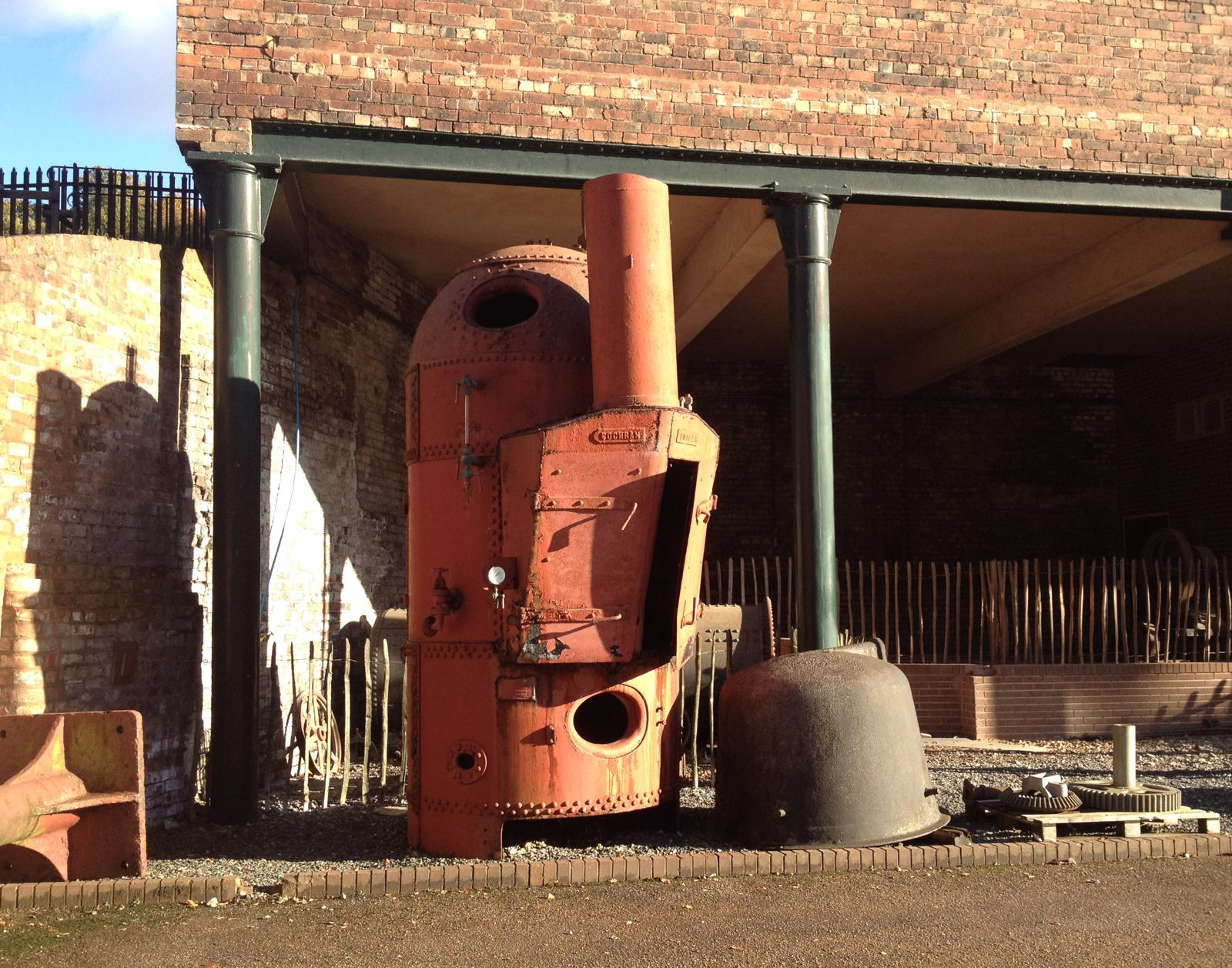 A big rusty orange boiler alongside other bits of old machinery