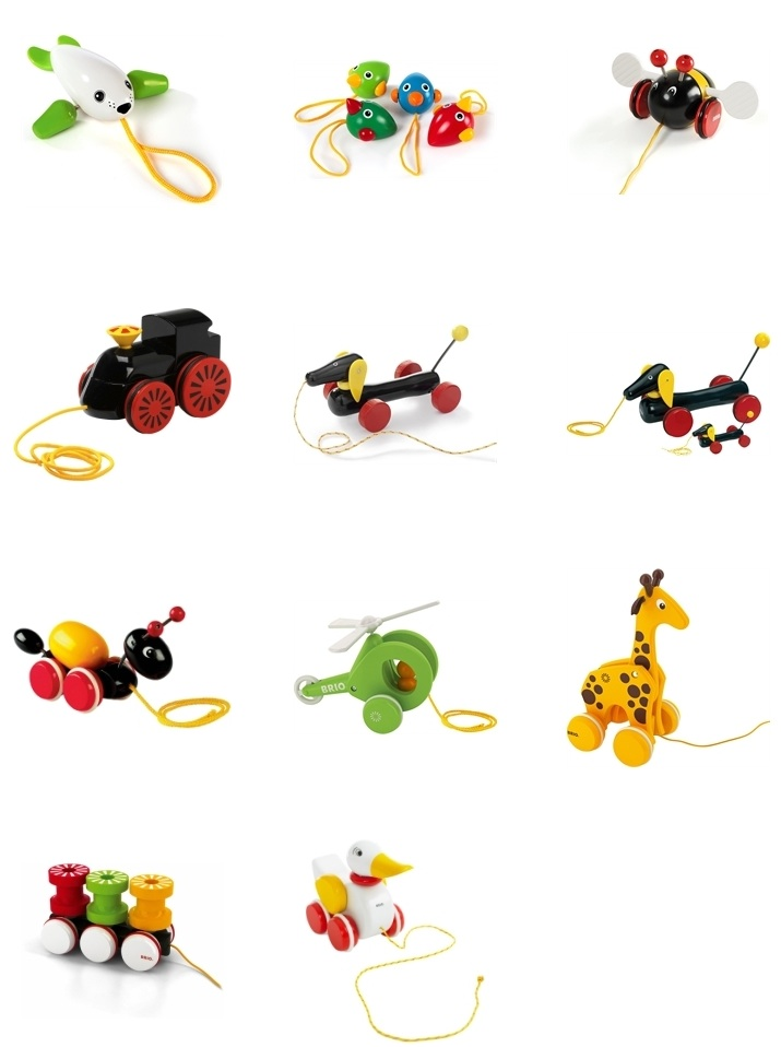 Eleven brightly-coloured wooden pull along toys: a seal, bird chicks, a bee, a steam engine, sausage dogs, an ant, a helicopter, a giraffe, a railway carriage and a white duck