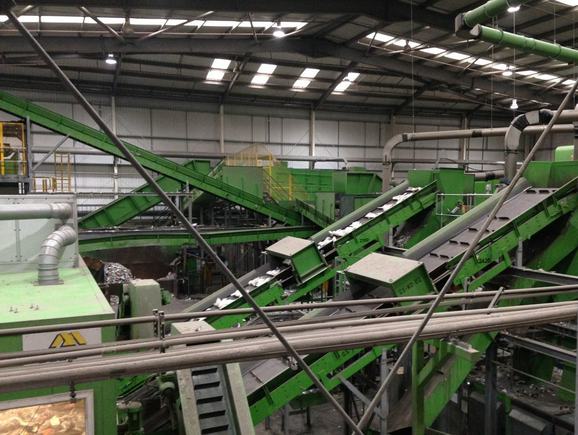 A warehouse of green conveyor belts and machinery