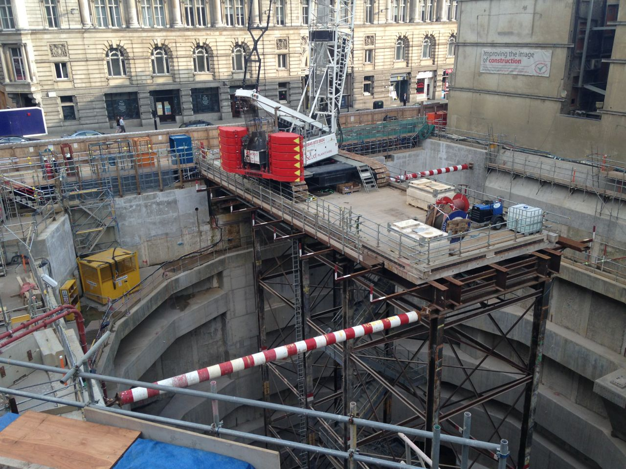 A concrete lined hole in the ground with a crane suspended above on steel scaffolding