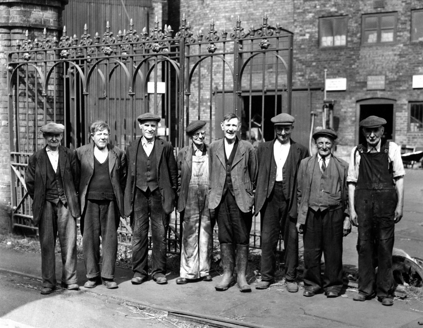Black and white photo of industrial workers standing proudly outside factory gates