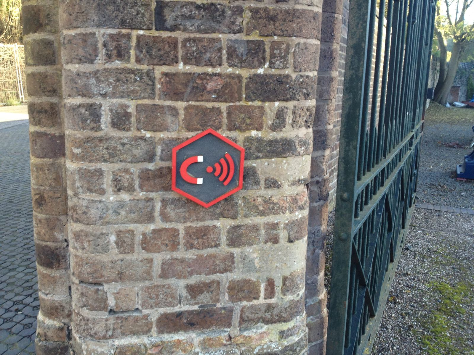 A hexagonal painted marker on a wall by some historic gates