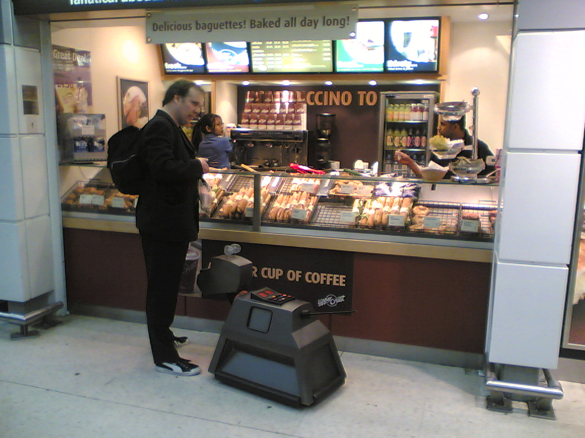 A man stands with a robot dog outside a baguette stand