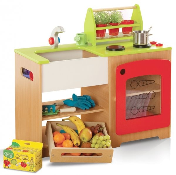 Toy wooden kitchen unit with a lime green work surface, sink, hob, oven and storage shelves. Shown with a wooden crate containing fresh fruit and pots of growing cress.