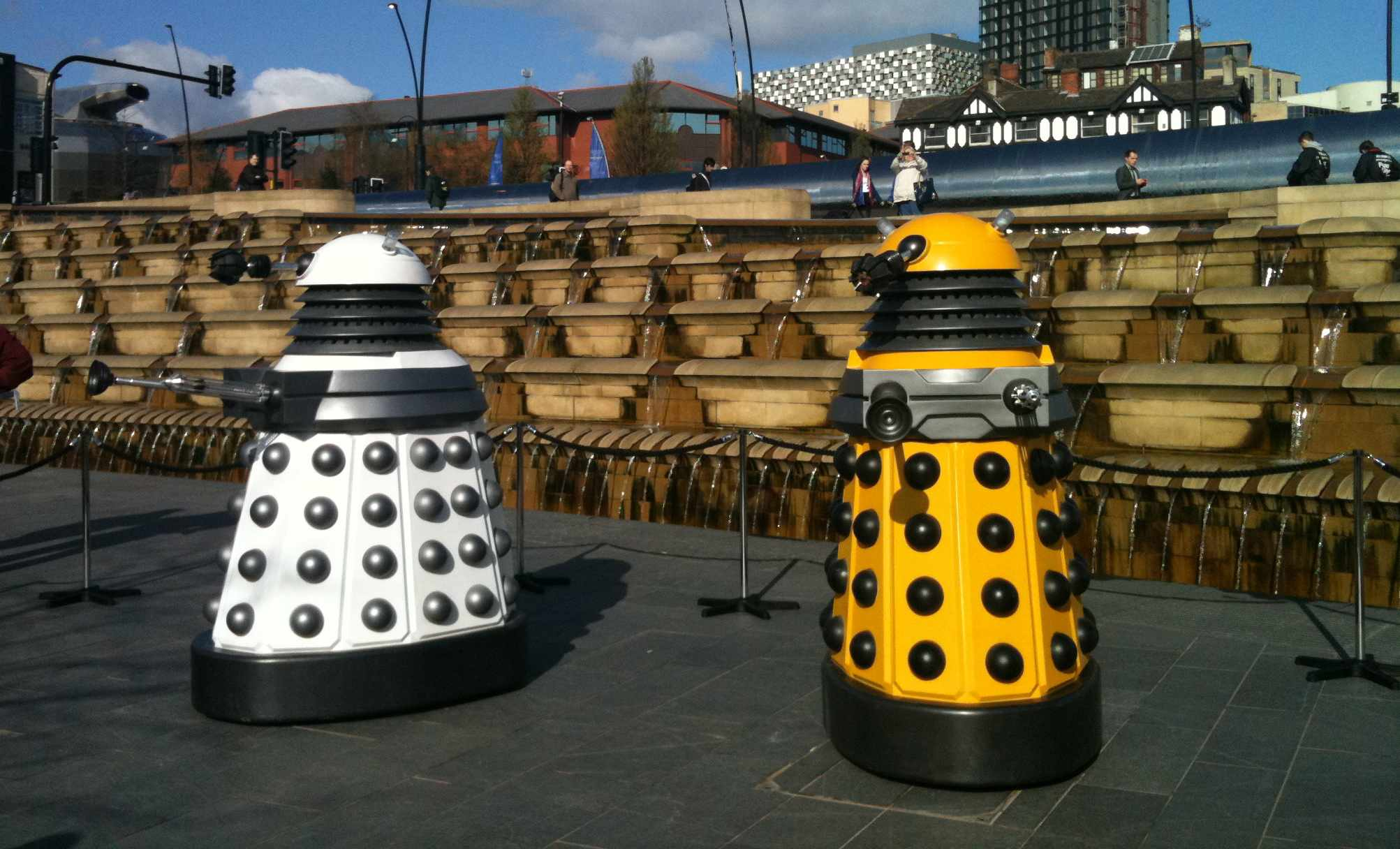 Two Daleks, one white and one yellow, in a public square